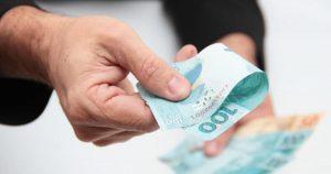 Foto de uma mão masculina oferecendo uma nota de cem reais, representando os detalhes para pedir um empréstimo