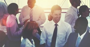 Foto de diversos empresários conversando e sorrindo, representando como se manter realizado no ambiente de trabalho