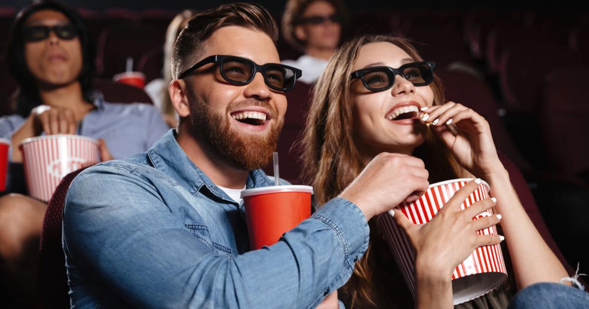 Foto de um casal comendo pipoca e sorrindo, representando como abrir um cinema