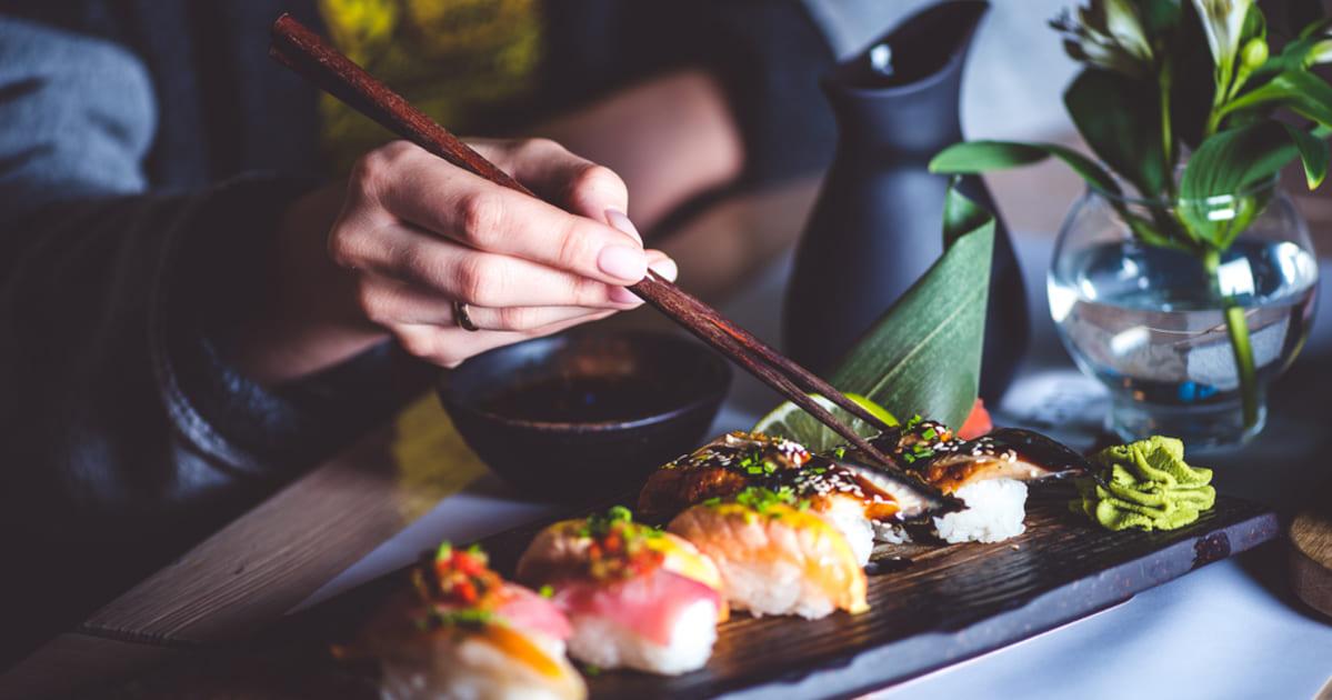 foto de uma pessoa comendo sushi com palitos, representando como abrir um restaurante japonês