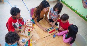 foto de uma mulher e várias crianças brincando, representando como abrir uma brinquedoteca