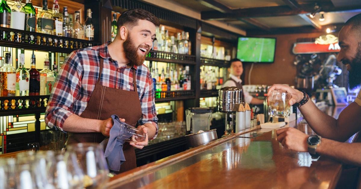 Foto de um garçom servindo um homem, representando como abrir uma cachaçaria