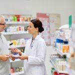 foto de uma mulher atendendo um homem com remedios atrás, representando como abrir uma drogaria