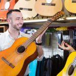 Foto de duas pessoas com violões na mão, representando abrir uma loja de instrumentos musicais