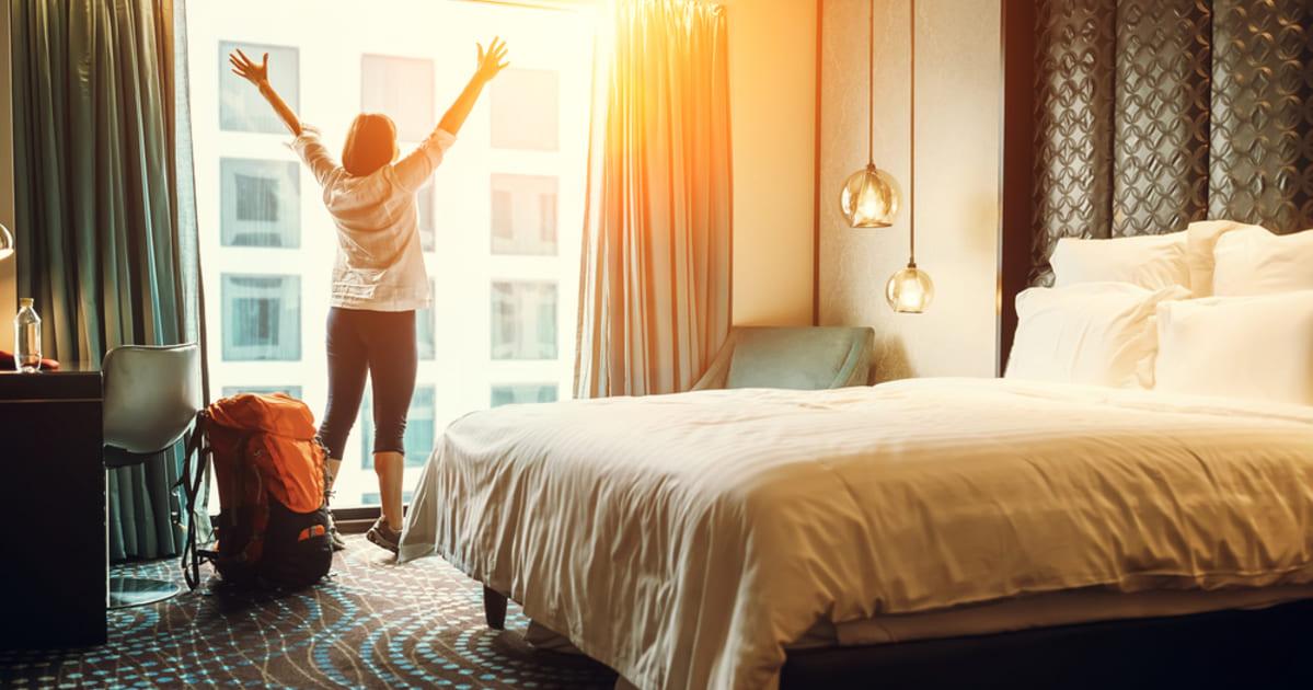 foto de uma mulher em um quarto de hotel, representando como abrir uma pousada