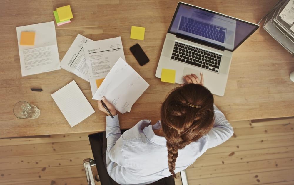 foto de cima, de uma mulher mexendo em um notebook e em alguns papéis, representando empreender em belo horizonte