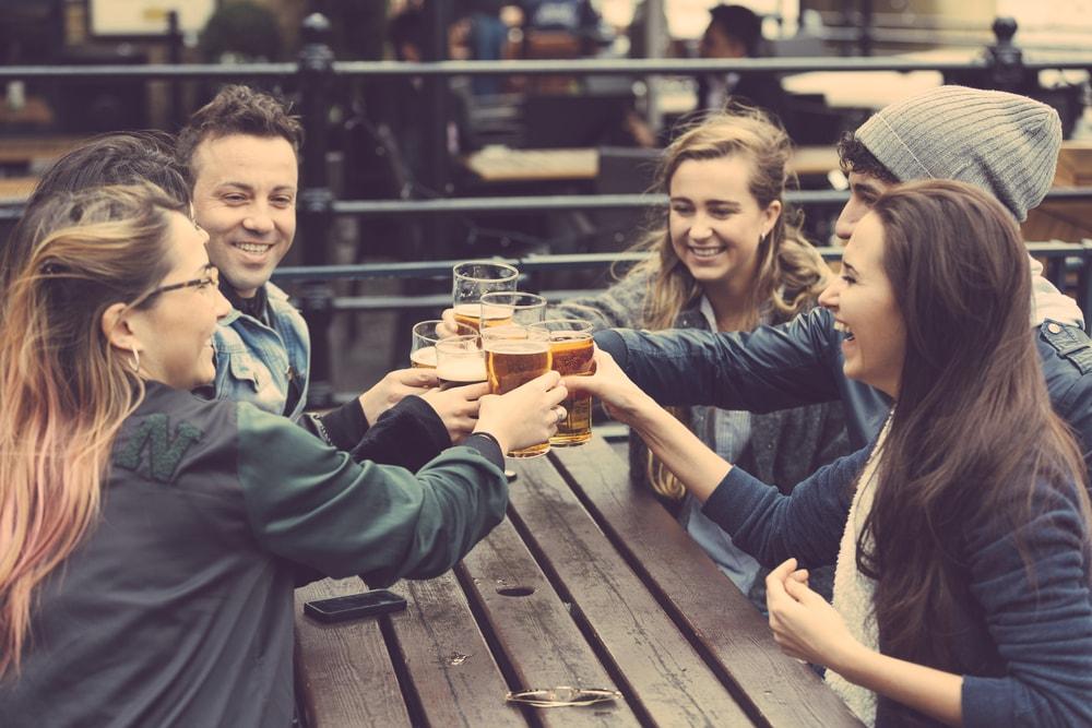 Foto de um grupo de amigos brindando, representando como abrir uma cachaçaria