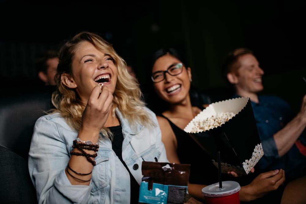 Foto de duas mulheres rindo e comendo pipoca, representando como abrir um cinema