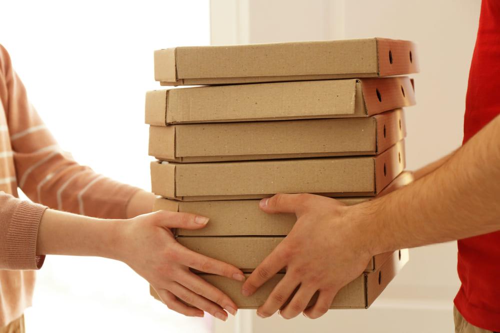 foto de uma pessoa entregando caixas de pizza, representando como abrir um delivery de comida