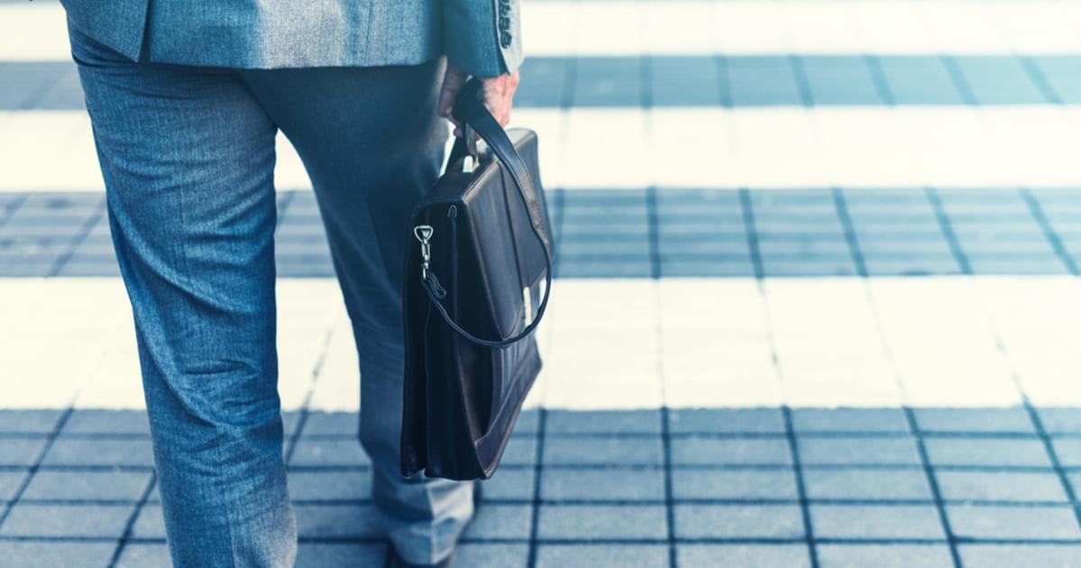 foto de um homem de terno andando com uma maleta na mão, representando como empreender em santos