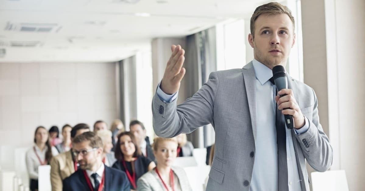 Foto de um homem falando ao microfone, representando como falar melhor