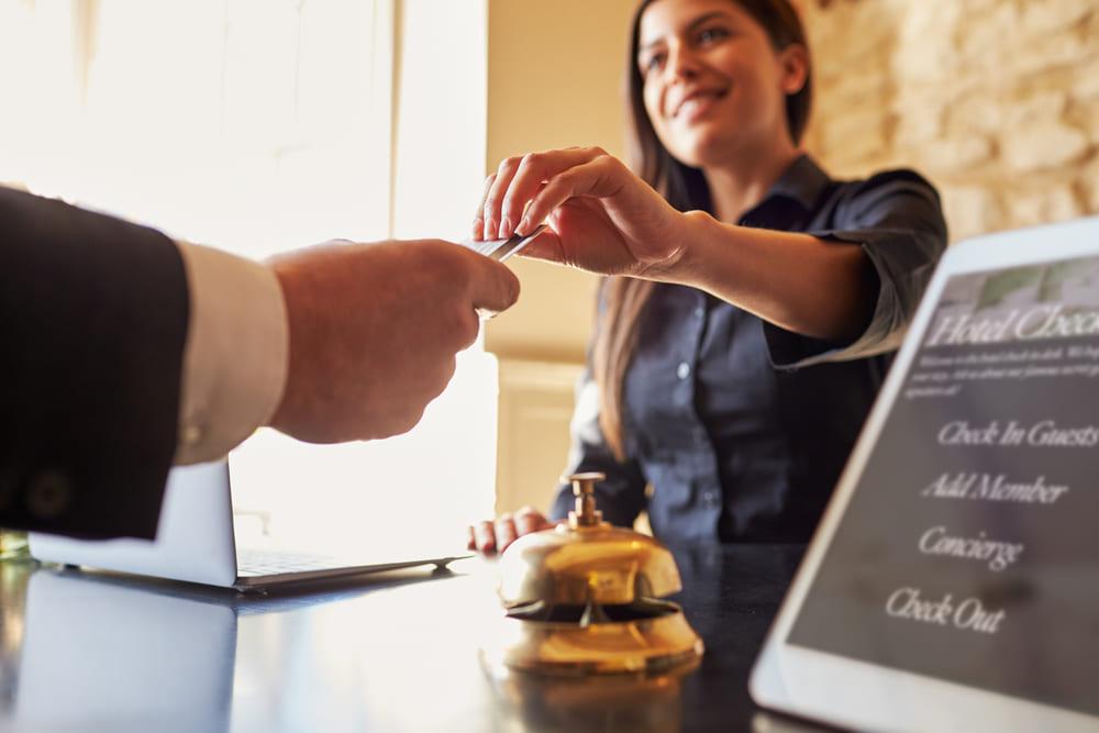 Foto de uma mulher entregando chave de quarto para um homem, representando como abrir uma pousada