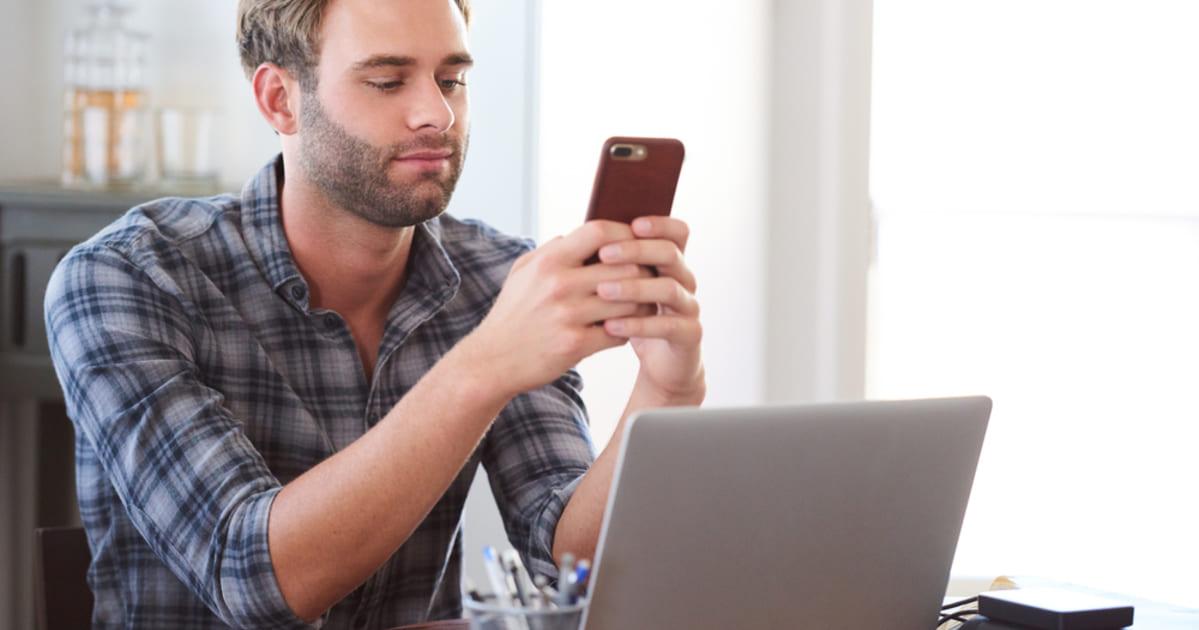 foto de um homem mexendo no celular enquanto trabalha, representando como parar de procrastinar