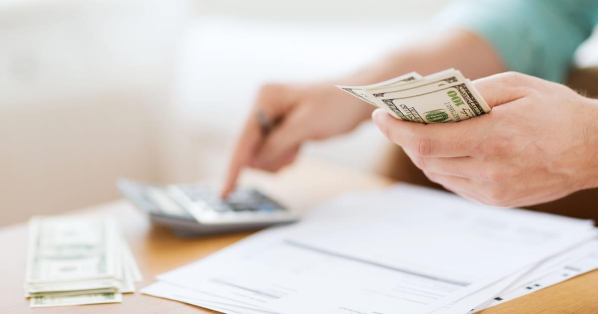 foto de uma pessoa contando dinheiro, representando a regra dos 50-15-30