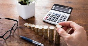 Foto de uma mão colocando moedas em uma pilha, com uma calculadora, caneta e vaso próximos, representando a taxa selic