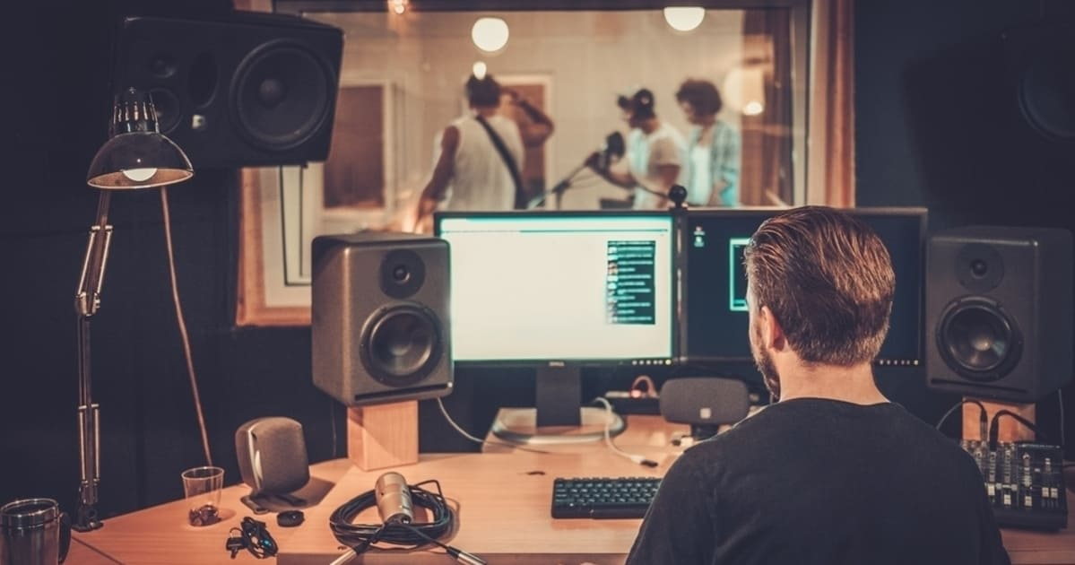 foto de um homem gravando uma banda, representando como abrir um estúdio musical