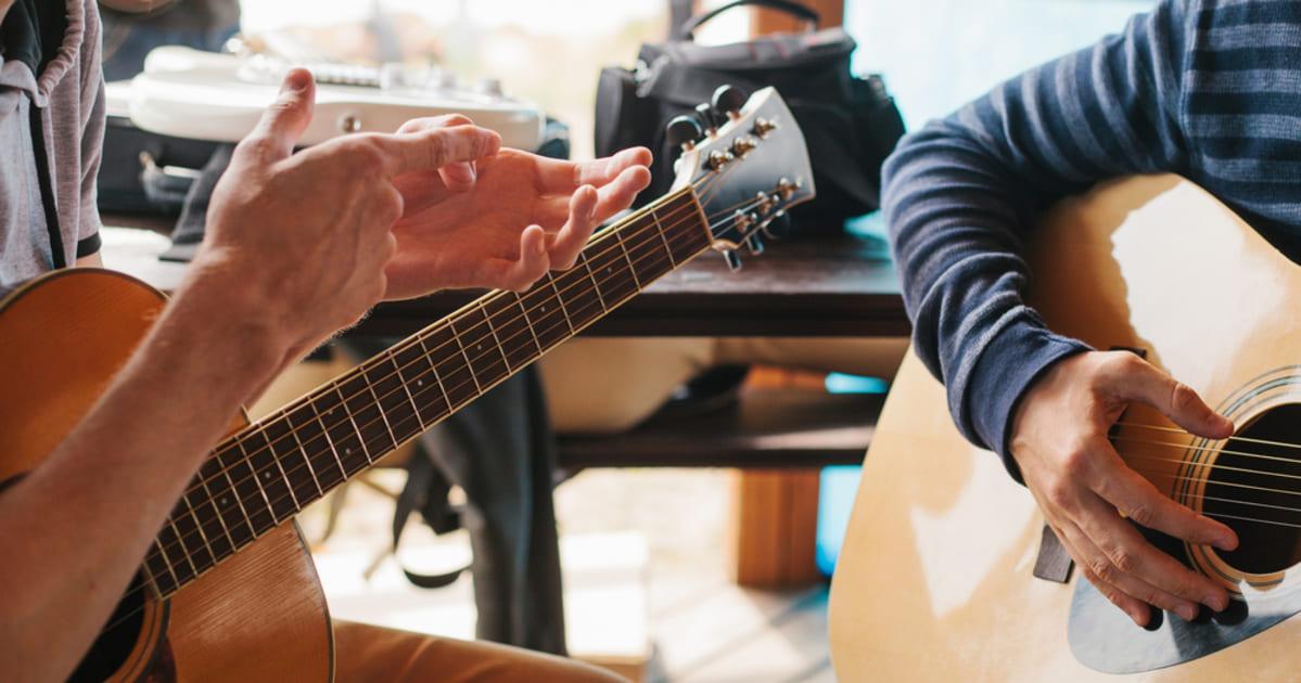 foto de duas pessoas tocando violão, representando como abrir uma escola de música
