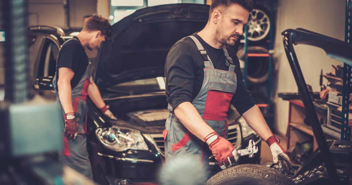 foto de dois homens arrumando um carro, representando como abrir uma oficina mecânica