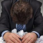 foto de um homem frustrado com vários papeis amassados em volta, representando o bloqueio criativo