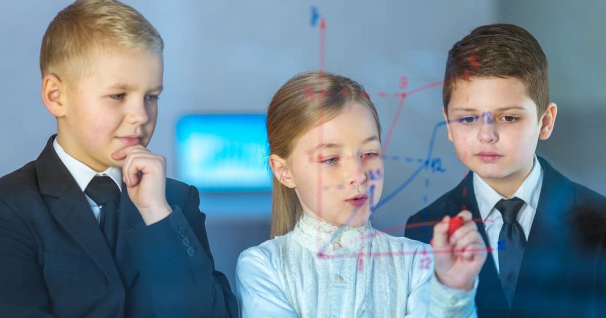 foto de três crianças, com roupas sociais e anotando um grafico, representando o empreendedorismo nas escolas