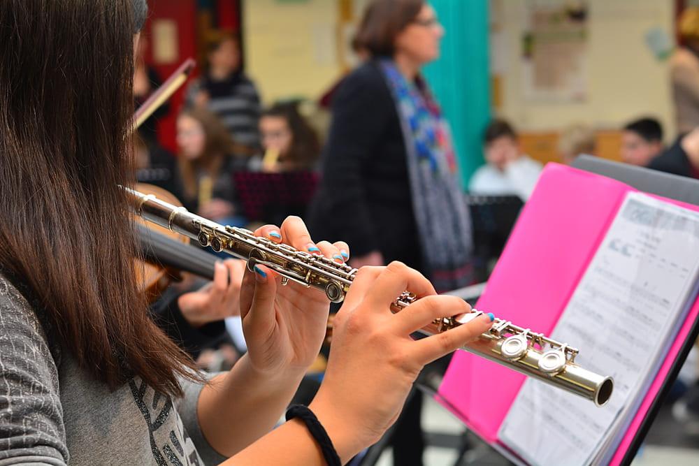 Foto de uma menina tocando flauta, representando como abrir uma escola de música