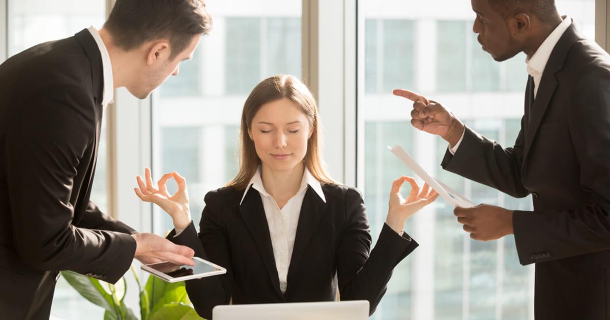 foto de uma mulher zen no meio de dois homens discutindo, representando a gestão de conflitos