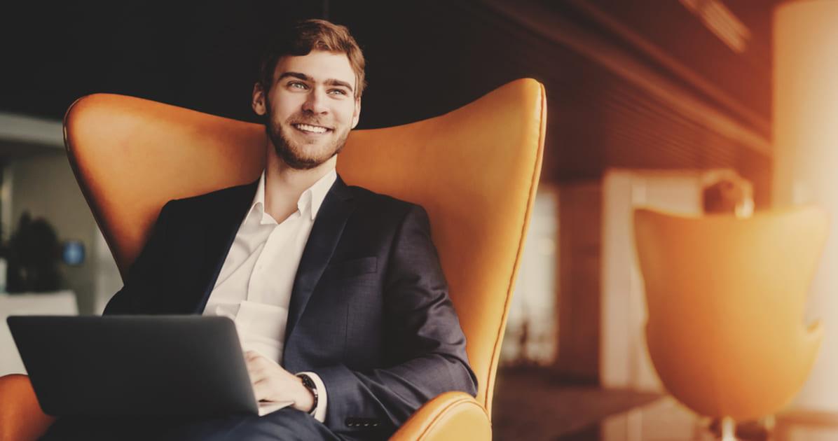 foto de um homem de terno e um notebook no colo sorrindo, representando o marketing pessoal