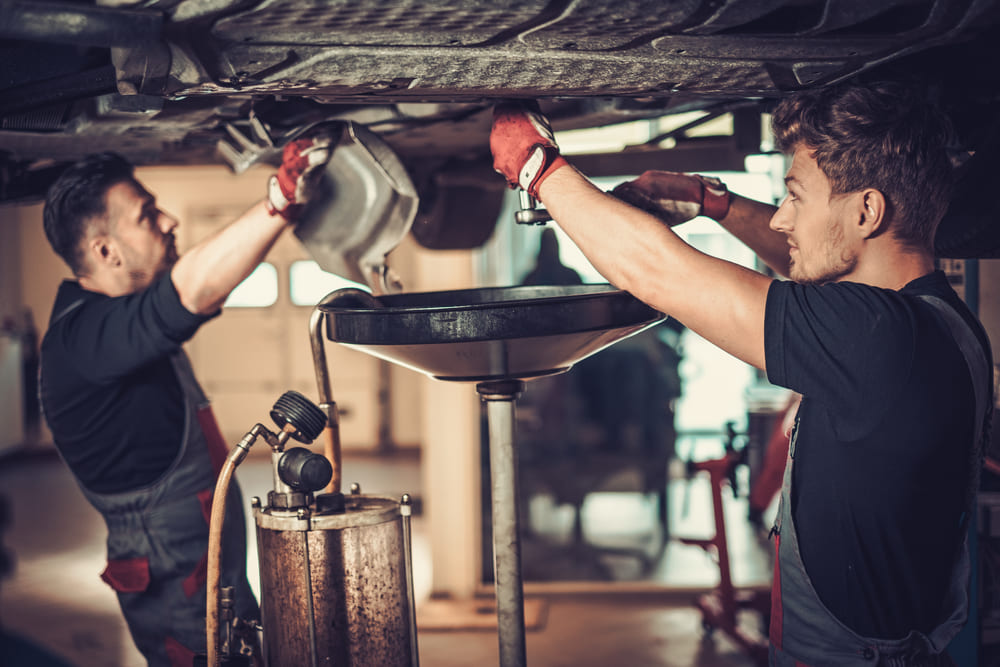 foto de dois homens concertando um carro por baixo, representando como abrir uma oficina mecânica