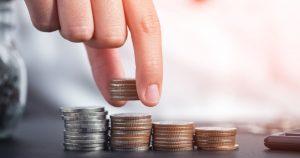 Foto de uma pessoa colocando moedas em montinhos, representando os juros na empresa
