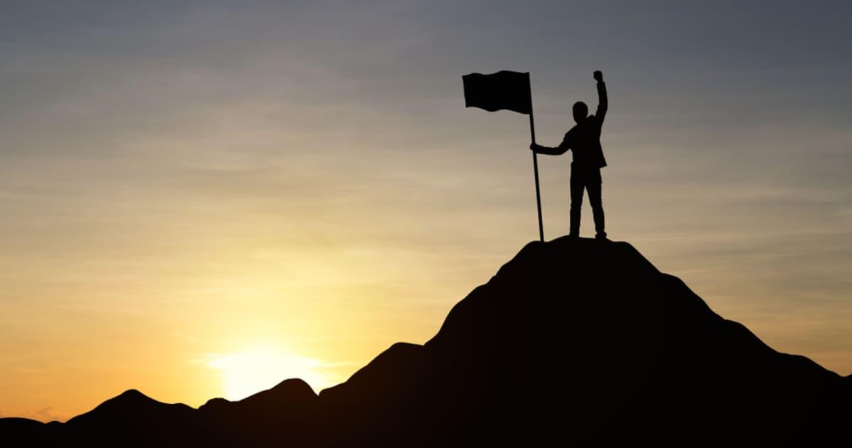 foto de um homem em cima de uma montanha com uma bandeira, representando os empreendedores de sucesso