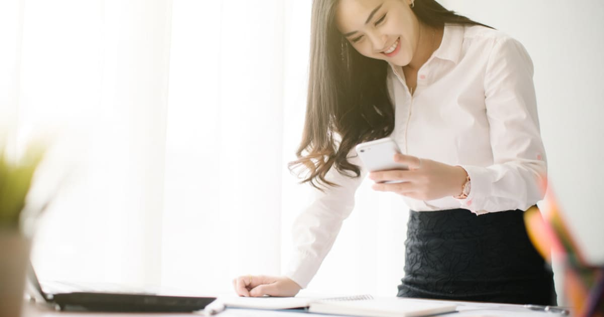foto de uma mulher olhando o celular, representando como empreender em caieiras