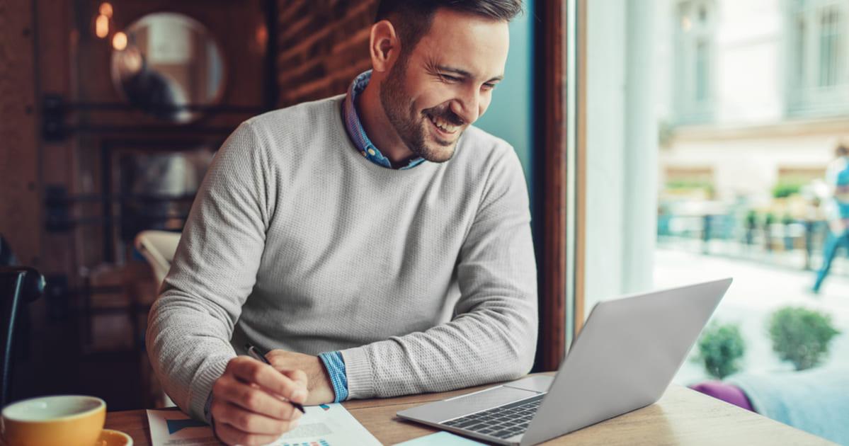 Foto de um homem sorrindo e mexendo em um notebook, representando empreender em Camaçari