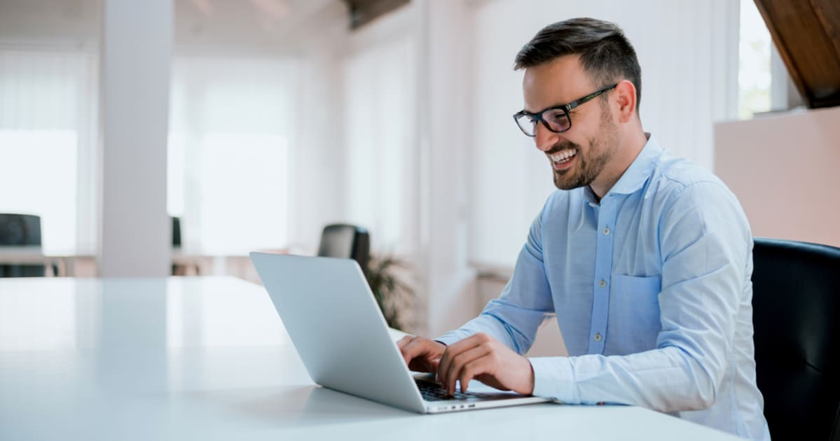 foto de um homem mexendo no notebook e sorrindo, representando como empreender em itatiba