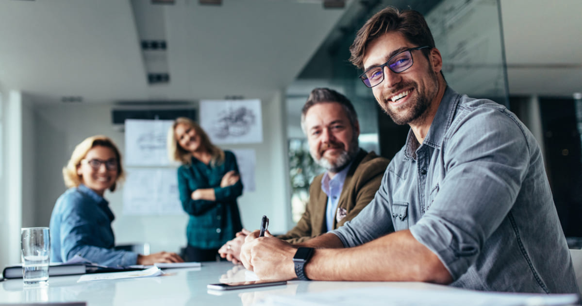 Foto de algumas pessoas sorrindo sentados em uma mesa, representando como empreender em são josé dos campos