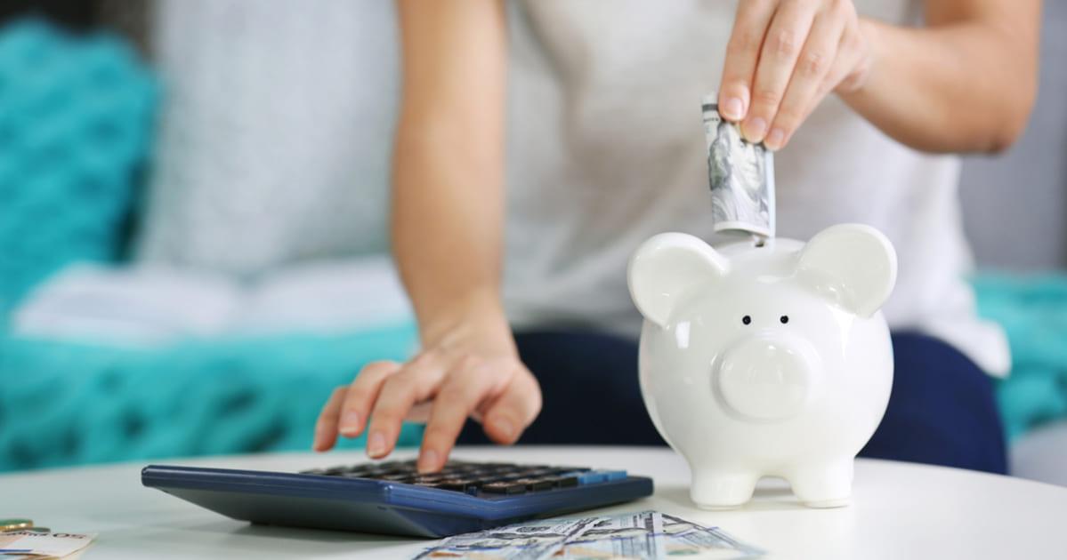 foto de uma mulher colocando dinheiro em um cofrinho, representando o investimento do fgts