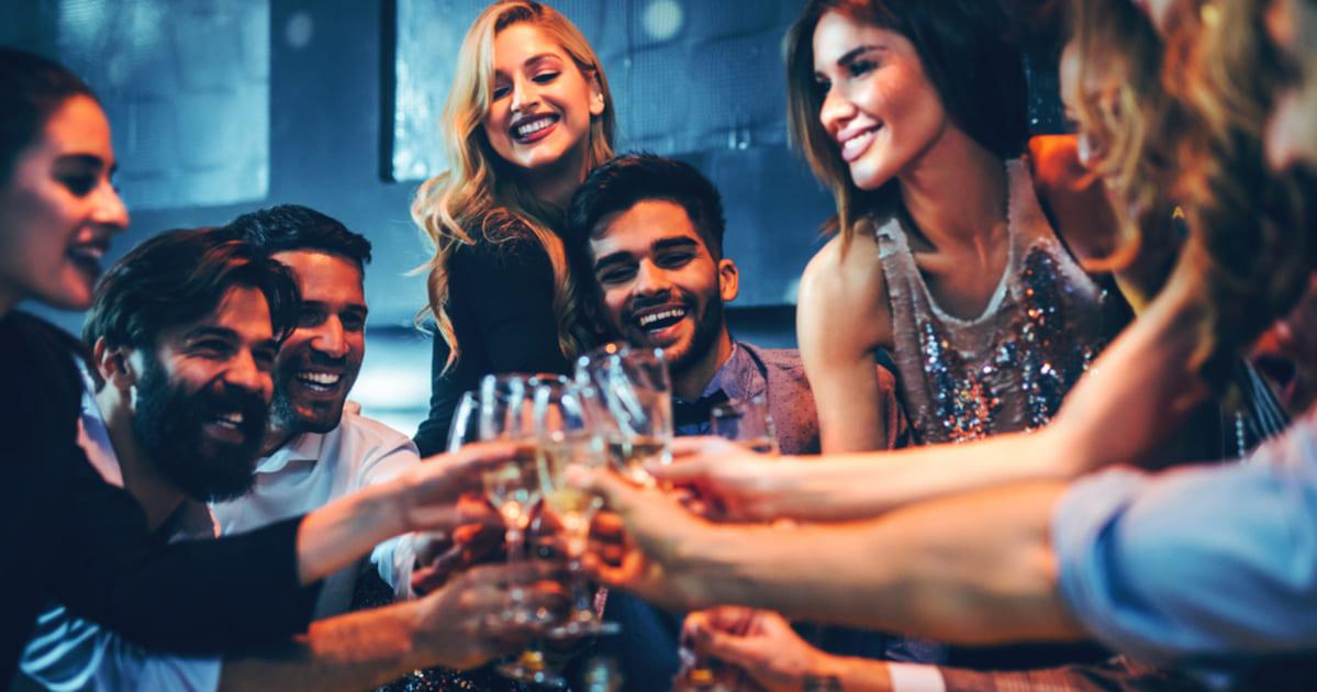 foto de várias pessoas comemorando com chapanhe, representando o happy hour