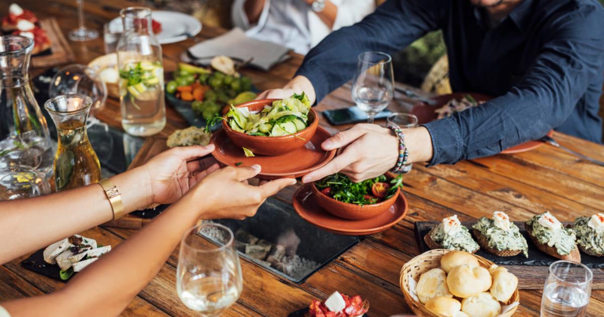 foto de pessoas comendo em uma mesa com pratos de refeições, representando como abrir um restaurante vegetariano