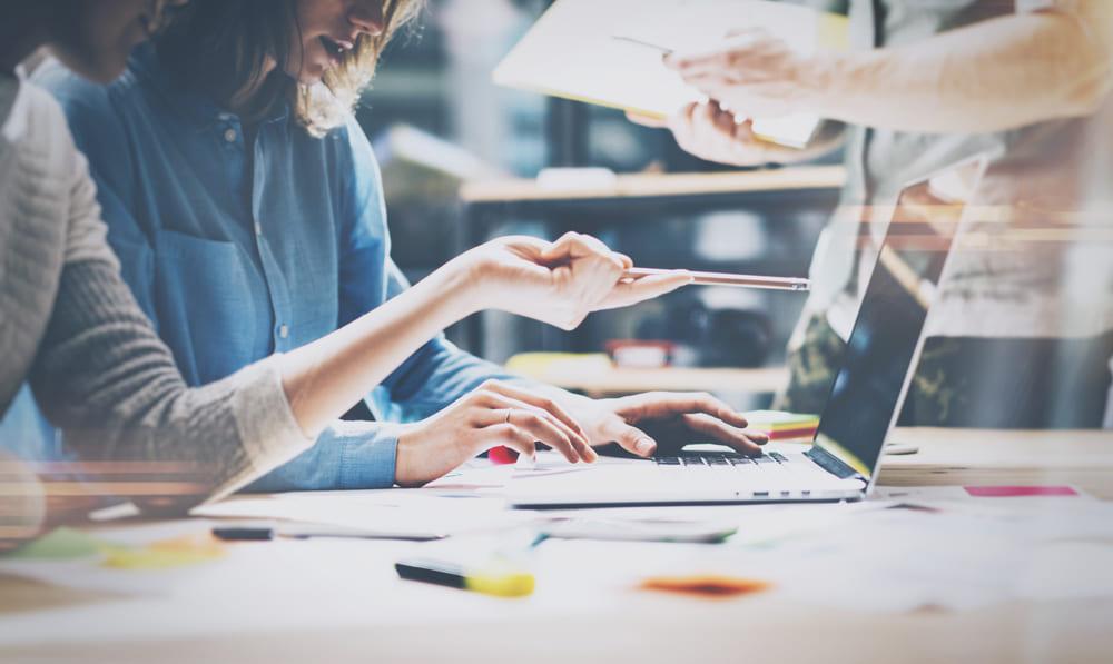 foto de duas pessoas analisando um notebook, representando a contabilidade consultiva