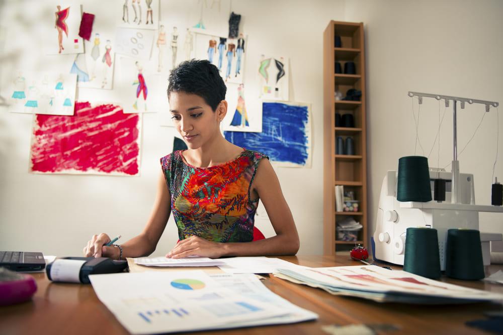 foto de uma mulher analisando gráficos em um atelier, representando as dúvidas do MEI