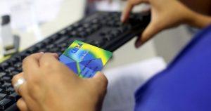 foto de uma pessoa segurando o cartão cidadão da caixa, representando o saque do pis
