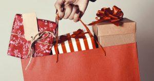 foto de uma mão feminina segurando uma sacola com presentes, representando a sazonalidade de vendas