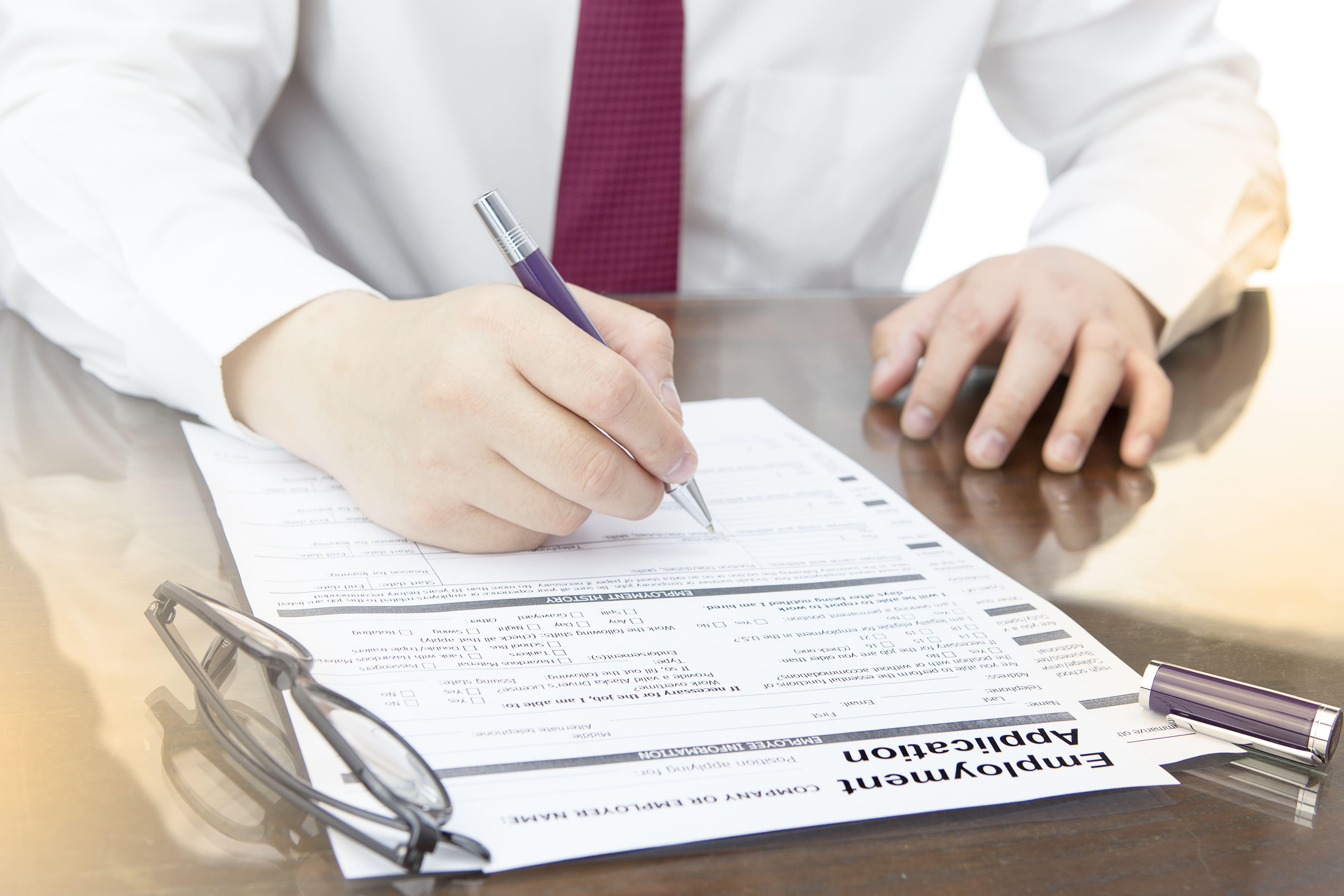 Imagem de uma pessoa preenchendo sua ficha de cadastro para quem quer abrir uma agência de emprego