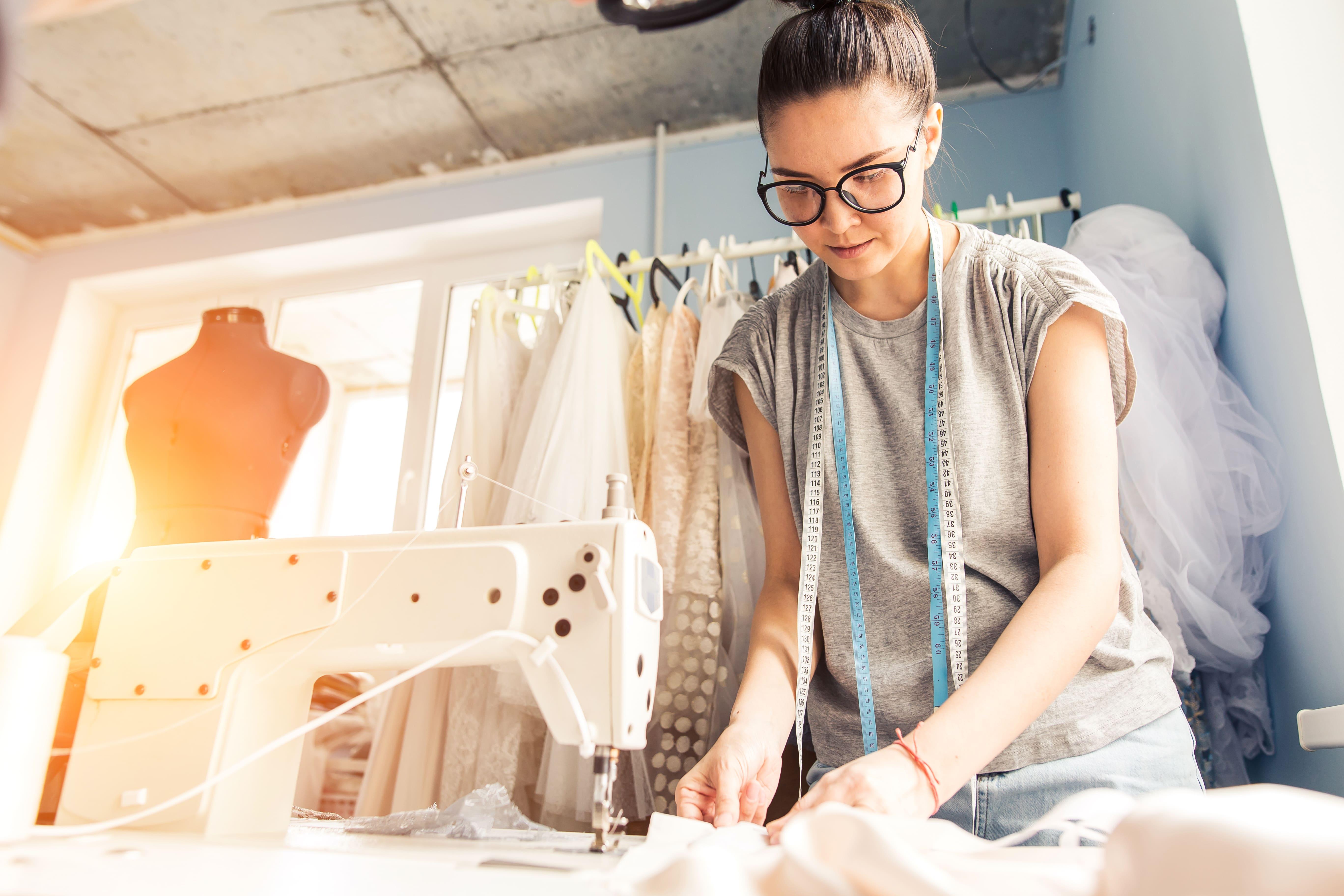 Imagem de uma mulher costurando para influenciar os empreendedores que querem abrir um ateliê de costura