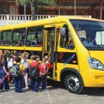 Crianças entrando no veículo, representando como trabalhar com transporte escolar