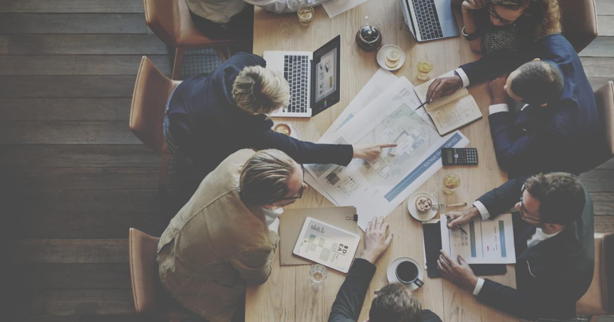 foto de várias pessoas sentadas a uma mesa com papeis e notebooks, representando como administrar uma empresa