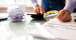 foto de um homem analisando uma nota fiscal com lupa, representando o caixa 2 e vender sem nota fiscal