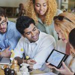 foto de pessoas reunidas analisando uma tela, representando os pequenos negócios
