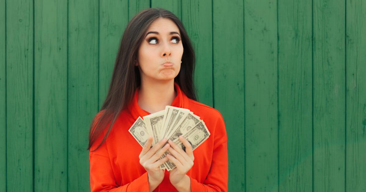 foto de uma mulher segurando algumas notas, representando como estar pronto financeiramente