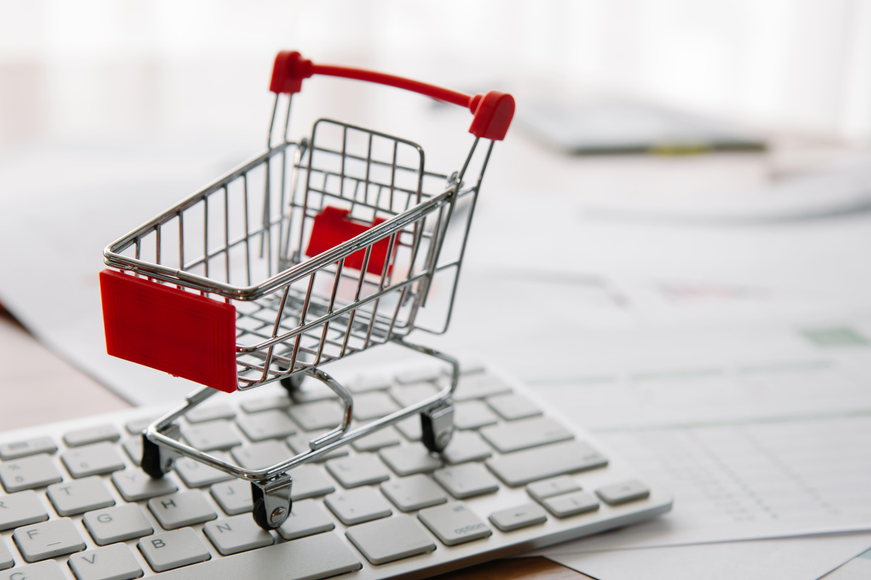 Imagem de um carrinho sob o teclado para remeter o e-commerce para contabilidade