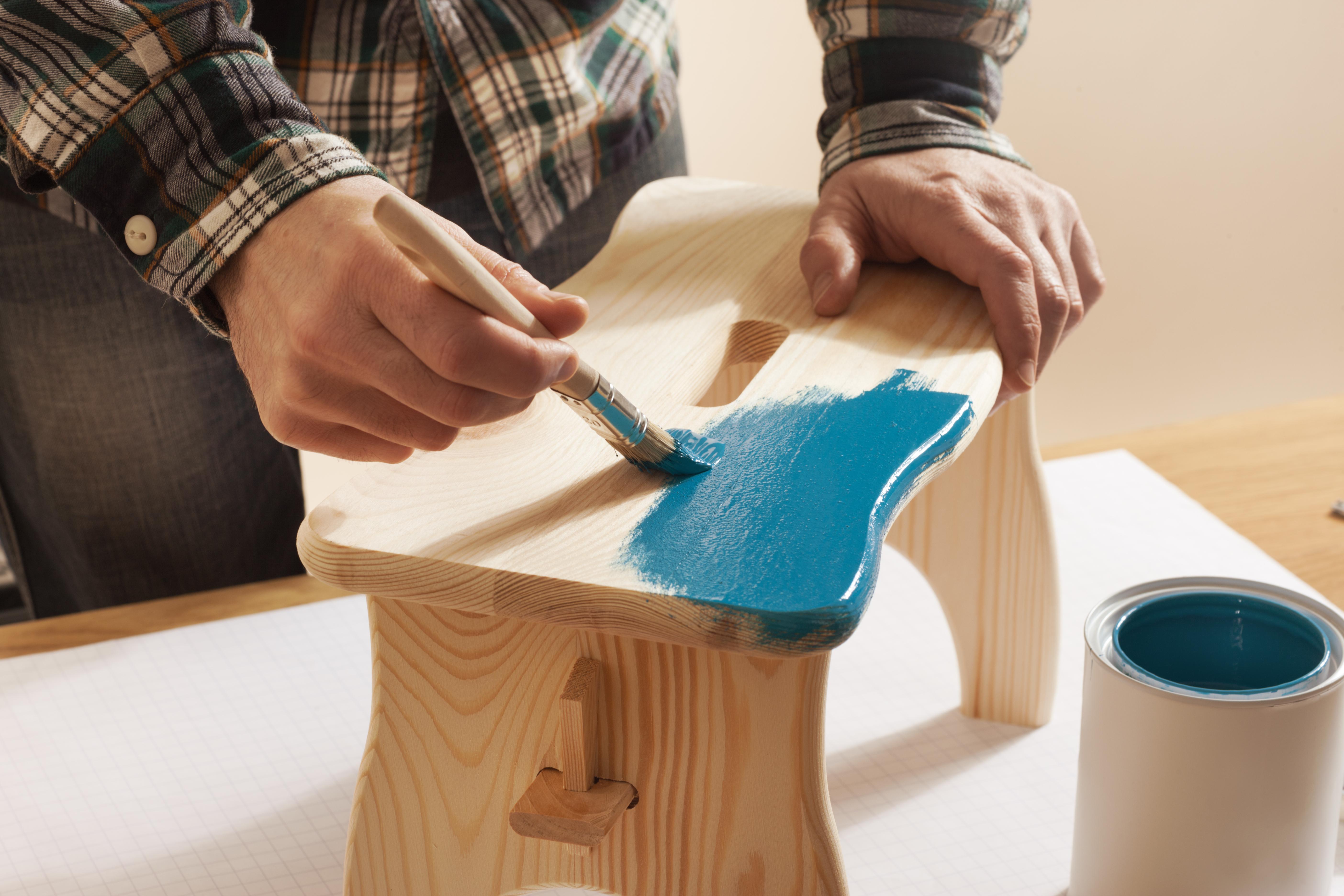 Imagem de uma pessoa pintando um banquinho para inspirar o empreendedor que deseja montar um serviço de restauração de móveis